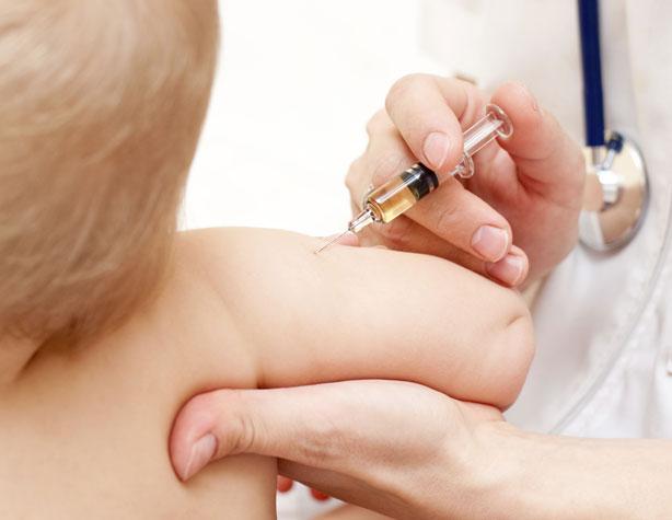 Un niño mientras le ponen una vacuna.