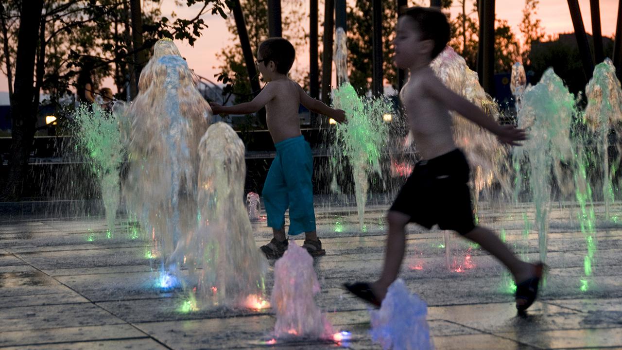Unos niños se refrescan en unas fuentes a causa del calor