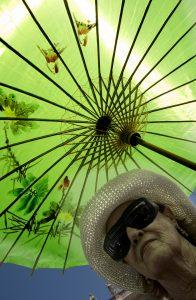 Una mujer se protege del sol con una sombrilla