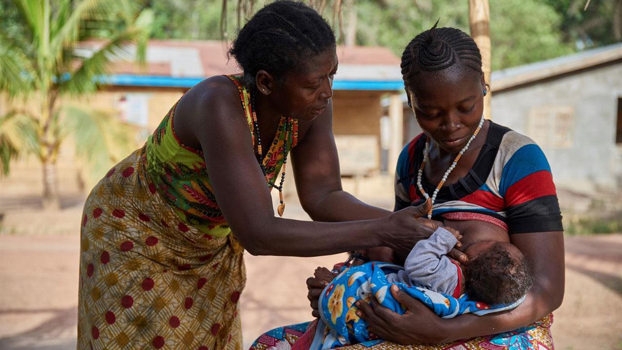 Una madre, ayudada a su vez por su madre, alimenta a uno de sus hijos gemelos de tres meses, en Sierra Leona. El agente de salud comunitario que trabaja en su pueblo es uno de los cerca de 15.000 que se encargan de acercar servicios de salud a sus comunidades.