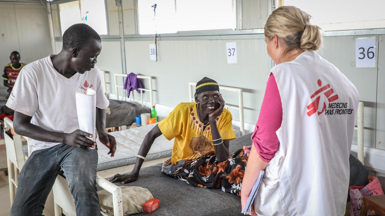 Nyandeng Goch, de 60 años, es de Wungdeng, a cuatro horas del Hospital de Agok, en Sudán del Sur. Goch fue mordida por una serpiente Bitis arietans en el pie. No mató a la serpiente porque la tradición dice que los ancestros viven en las serpientes. Con la ayuda de sus vecinos realizaron un agujero en la tierra y esperó dos horas. La creencia sostiene que este método tradicional detiene la propagación del veneno.