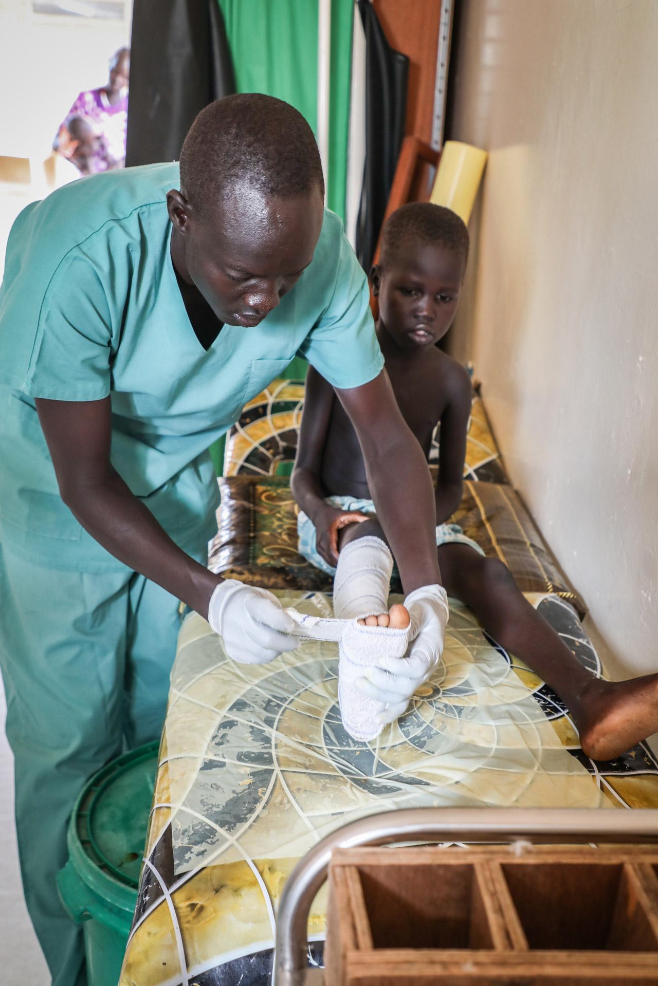 Un enfermero de MSF cambia los vendajes de un paciente de seis años mordido por una serpiente en el Hospital de Agok, en Sudán del Sur.