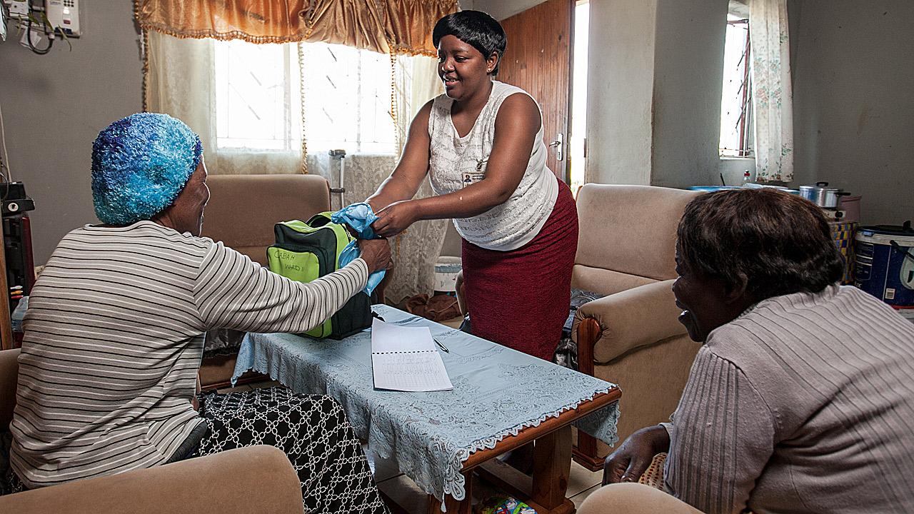 Una cuidadora de la comunidad entrega el tratamiento antirretroviral a una paciente en Sunnydale, Eshowe, KwaZulu-Natal.