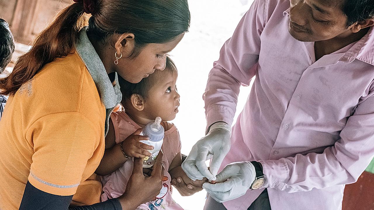 Un trabajador de salud hace la prueba de la malaria a un niño pequeño en la provincia de Battambang, en Camboya.