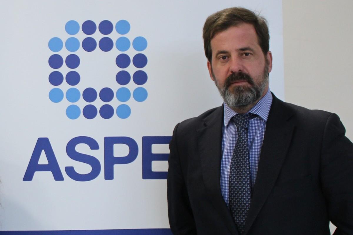 Carlos Rus, presidente de ASPE, delante del logotipo de la entidad