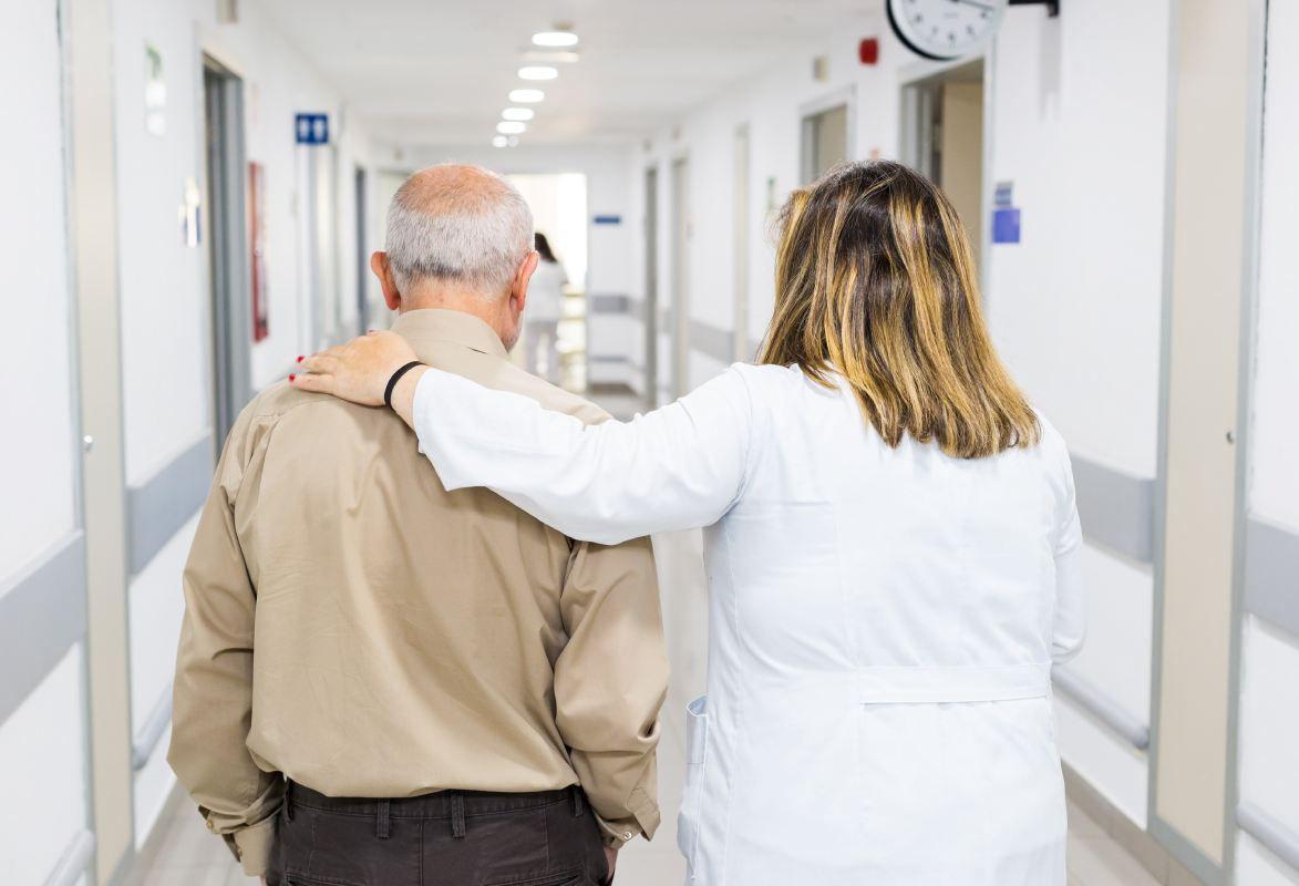 Enfermera acompaña a anciano, de espaldas, en un pasillo de hospital