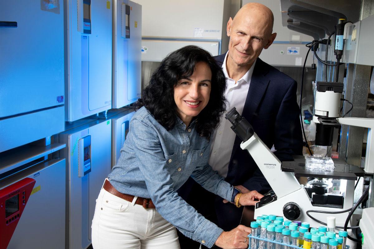 Los investigadores del Instituto Salk Concepción Rodríguez Esteban y Juan Carlos Izpisúa posan con un microscopio.