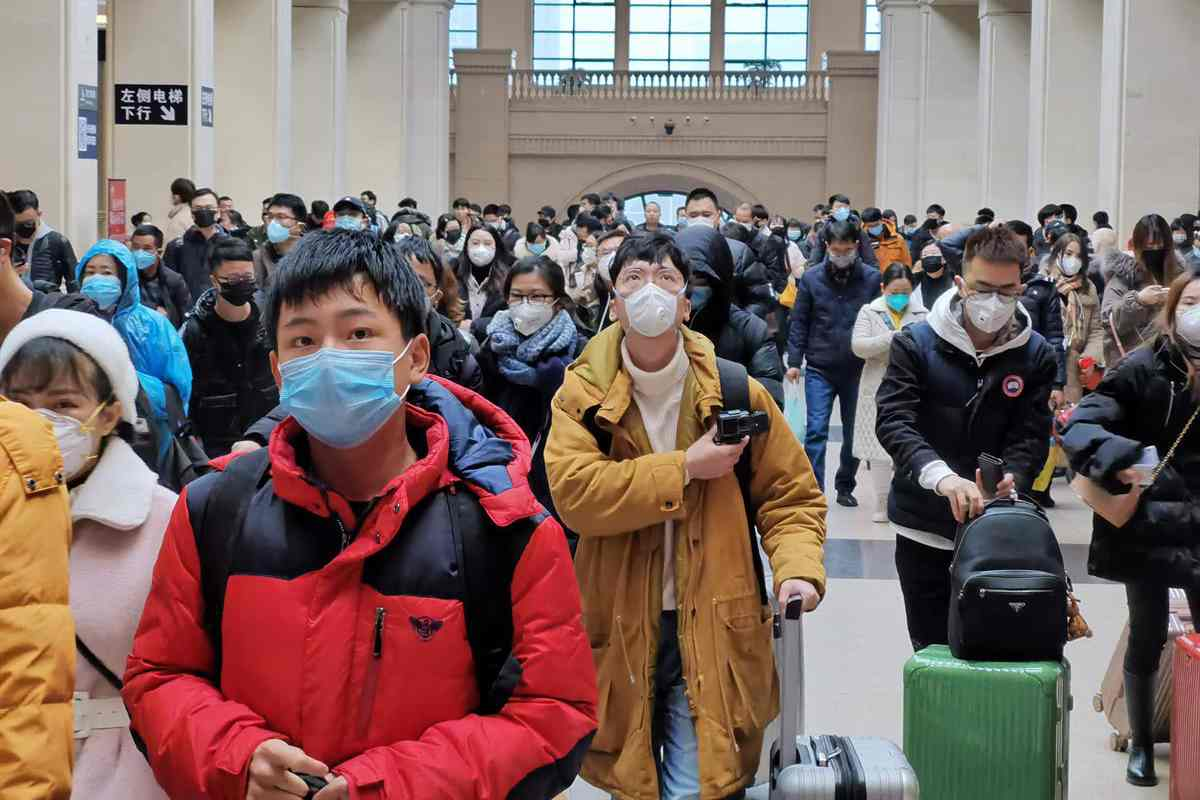 Un grupo de personas con mascarilla consulta los horarios de una estación de trenes.