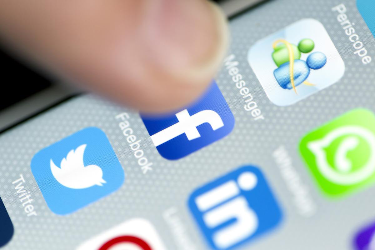 Dedo tocando la pantalla del móvil en el icono de facebook