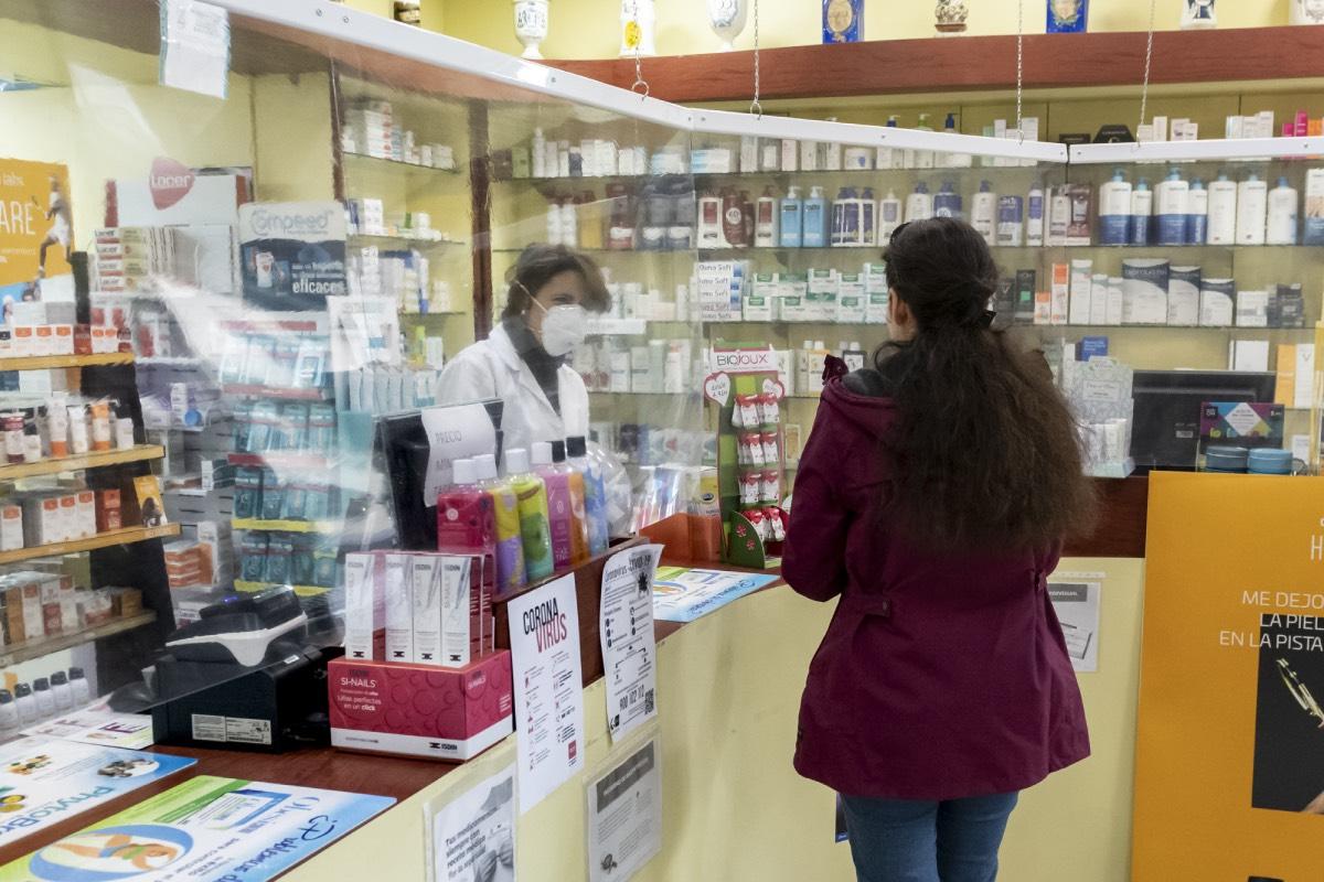 Una farmacéutica atendiendo con mascarilla. / J.L. Pindado
