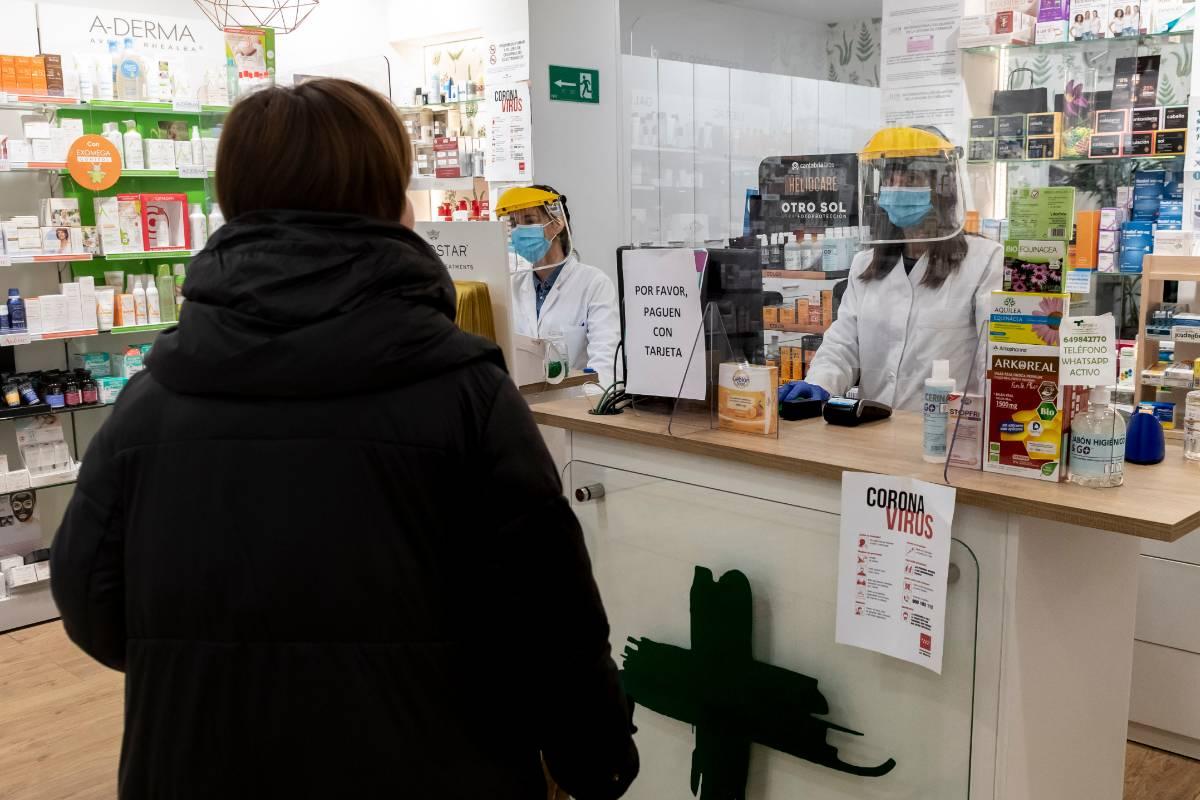 Dos farmacétuicas con protección atendiendo a una usuaria./ J.L. Pindado.
