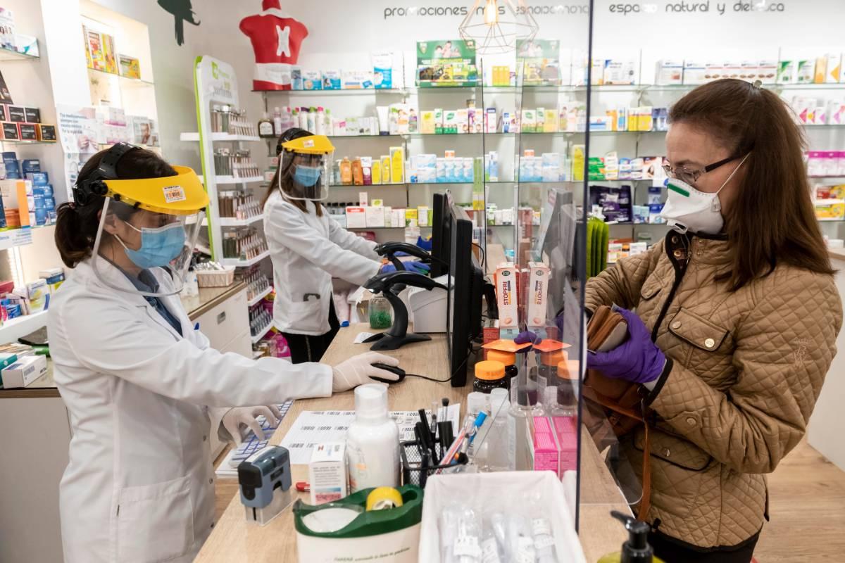 Dos farmacéuticas, con mascarilla y pantalla, atendiendo a una usuaria. / JL.Pindado.