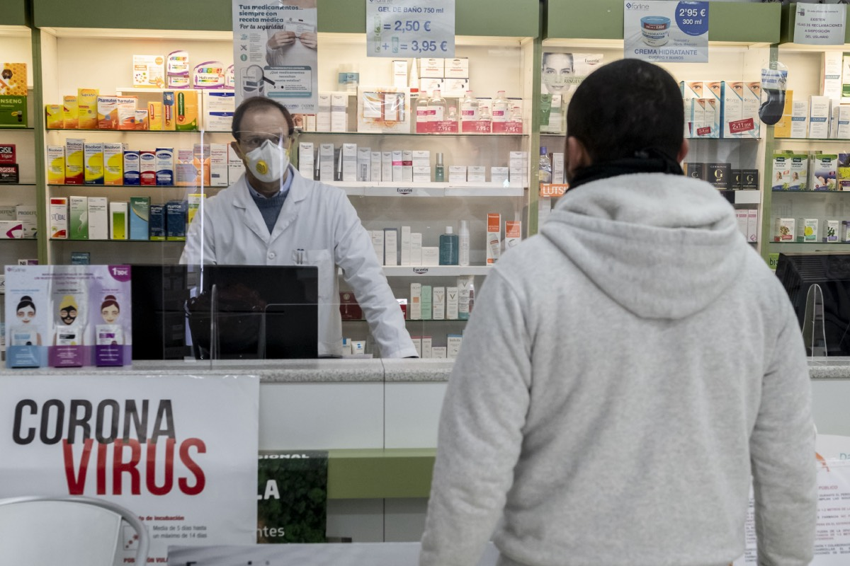 Farmacéutico con mascarilla atendiendo a un cliente. / J. L. Pindado