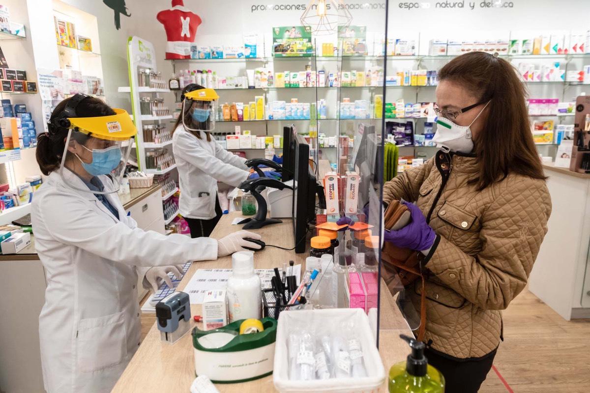 Farmacétuica y usuaria de una botica de Madrid, ambas con mascarilla. / J. L. Pindado.