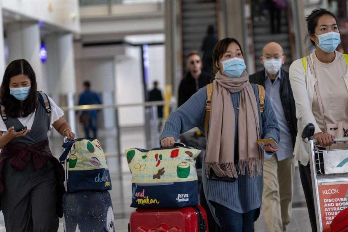 Viajeros con mascarilla para evitar contagios por coronavirus chino, en el aeropuerto Hong Kong.