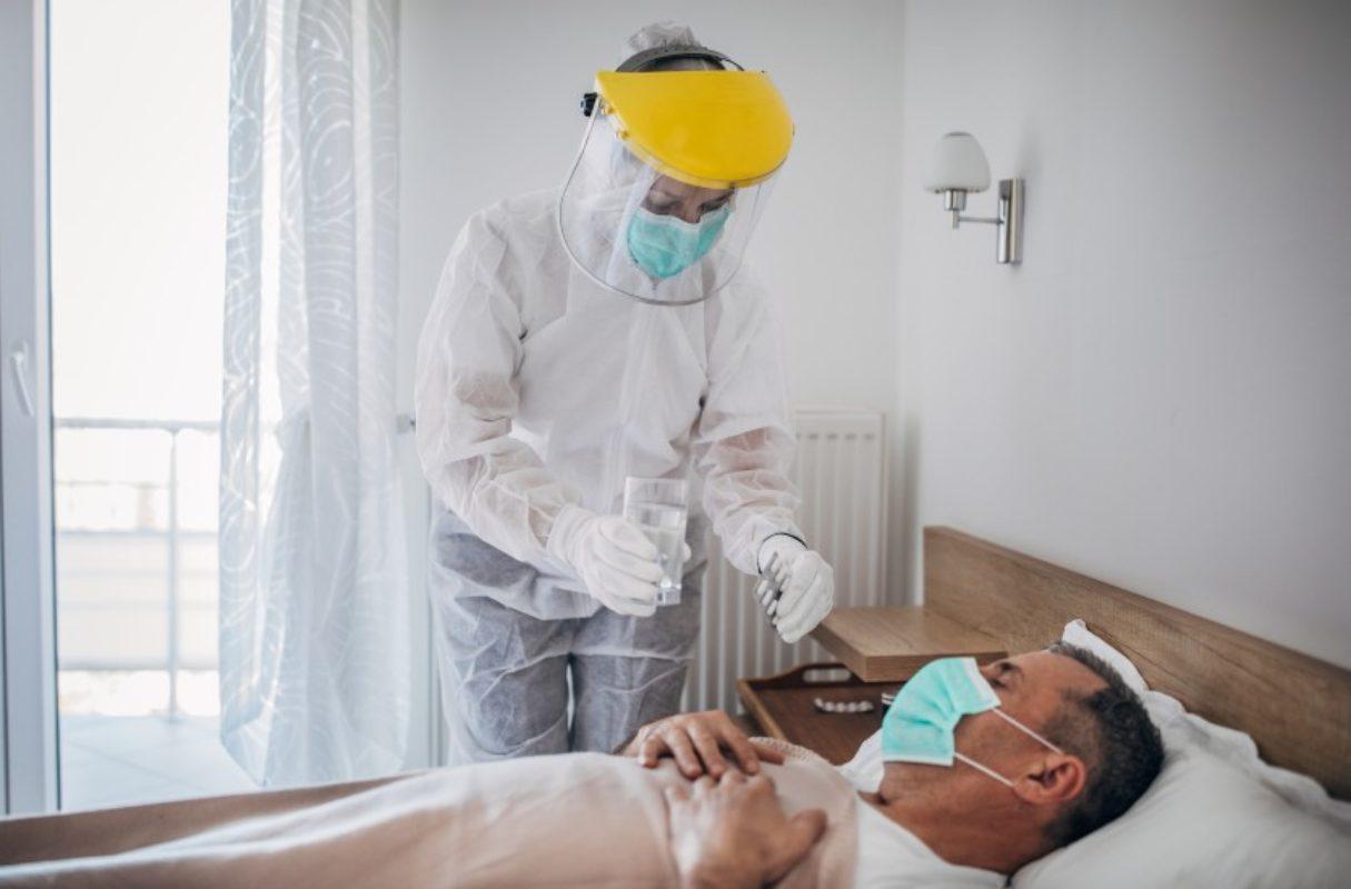 Profesional sanitario equipado con protección atiende a un paciente encamado.