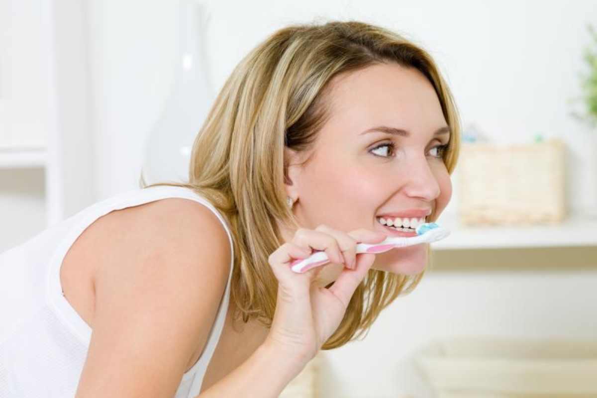 Una mujer se lava los dientes.