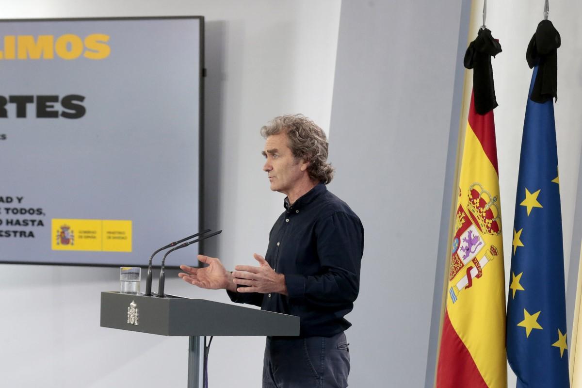 Fernando Simón en rueda de prensa, delante de banderas con crespón negro.