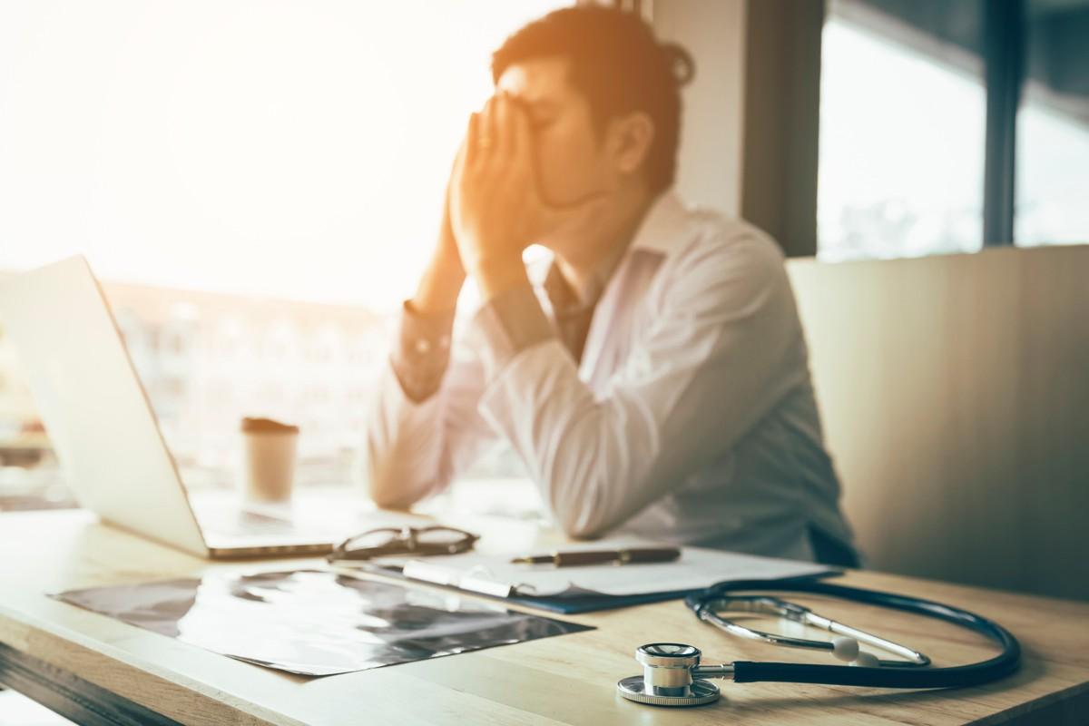 Médico autónomo estresado ante un ordenador portátil