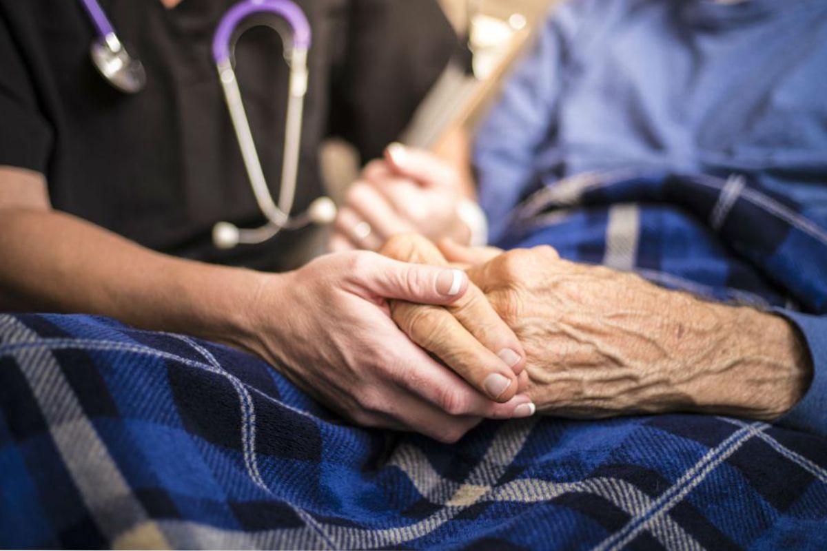 Un enfermo de Párkinson con su cuidador.