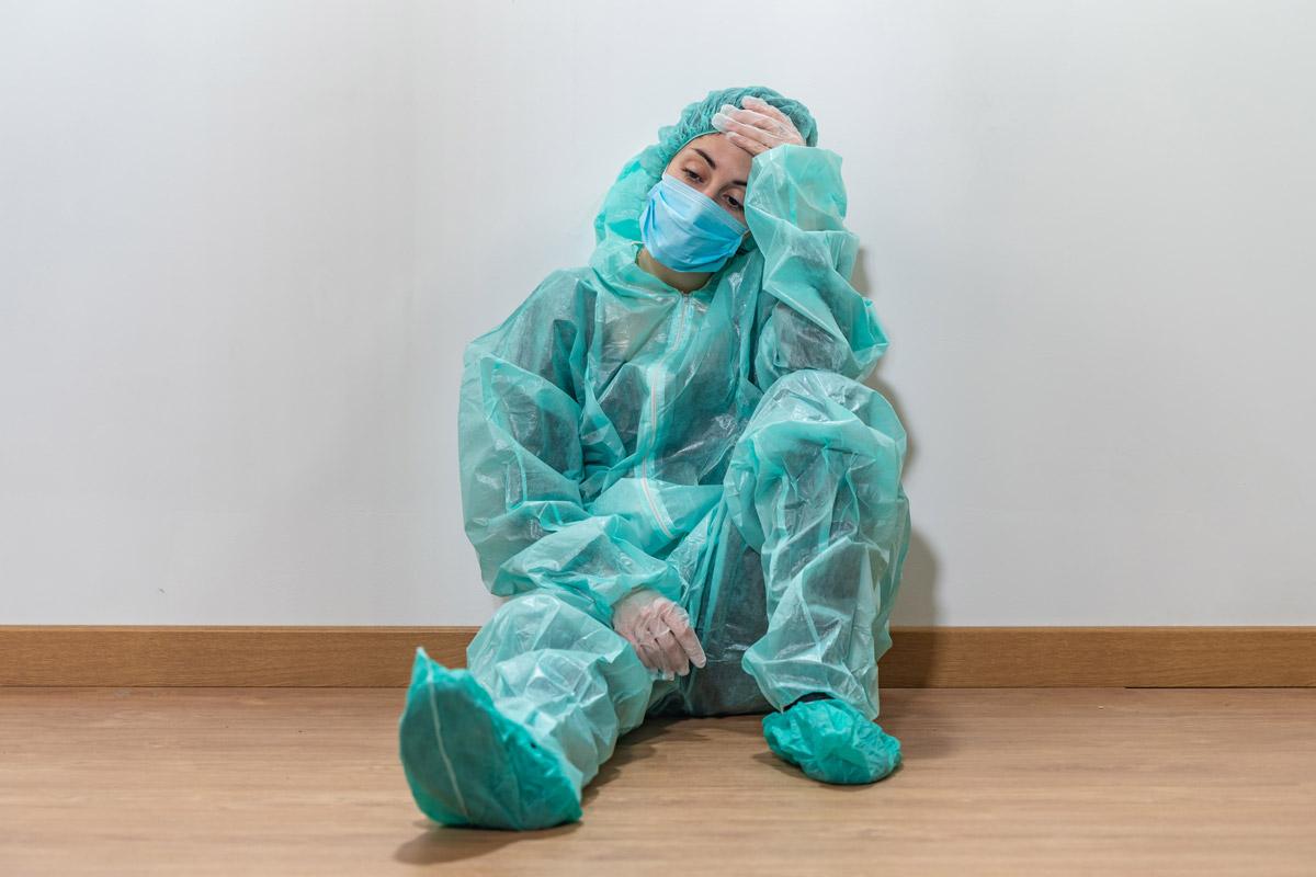 Profesional sanitario con EPI sentado en el suelo