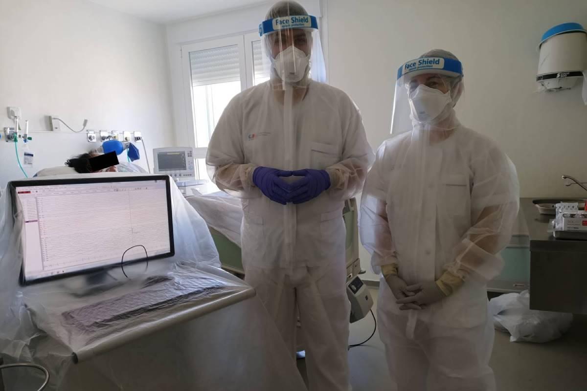 Dos enfermeros realizan una EEG en la UCI.