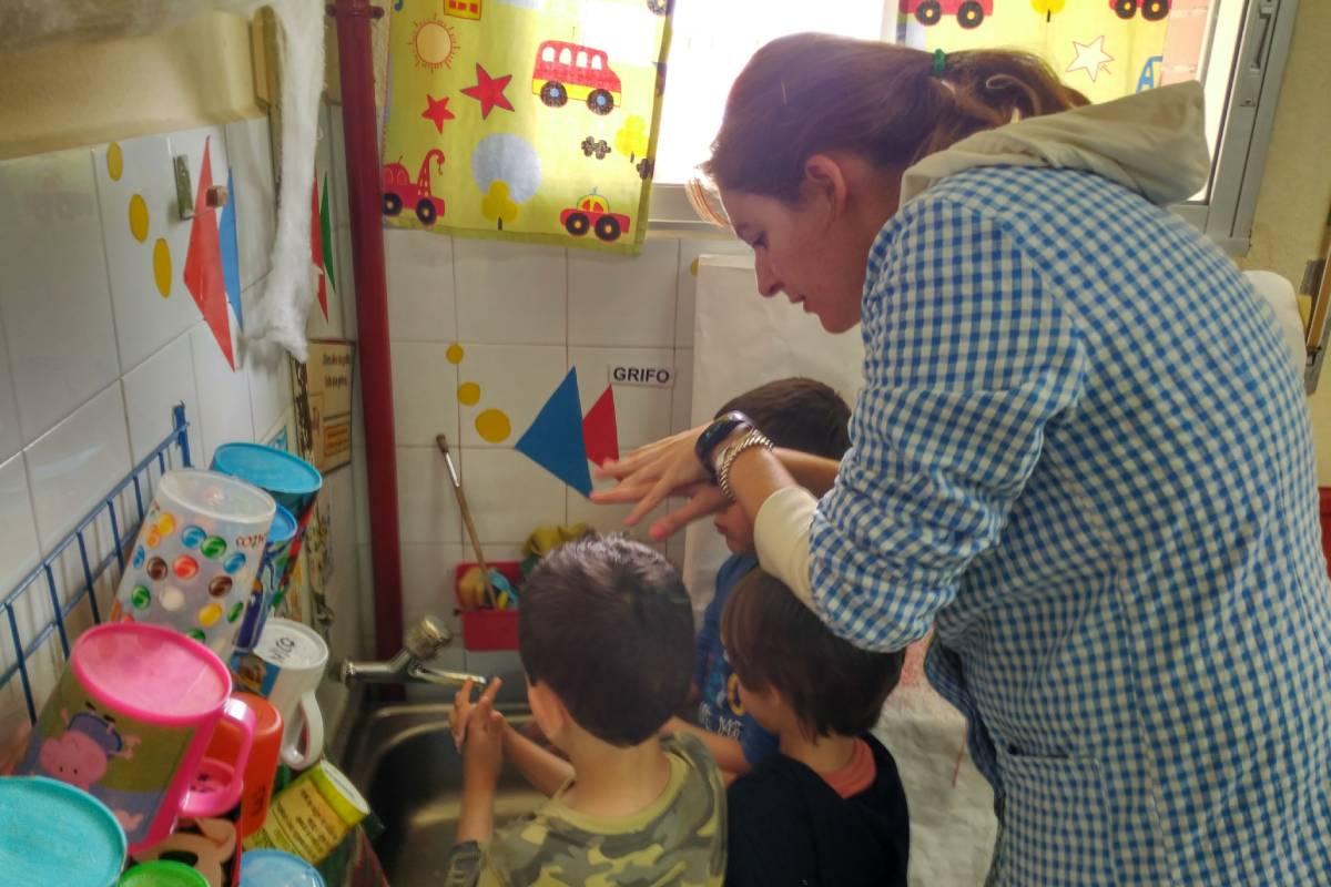 Una enfermera escolar enseñando a unos niños a lavarse las manos.