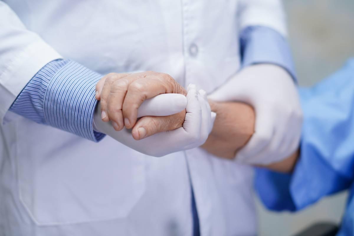Sanitario sujetando mano de enfermo