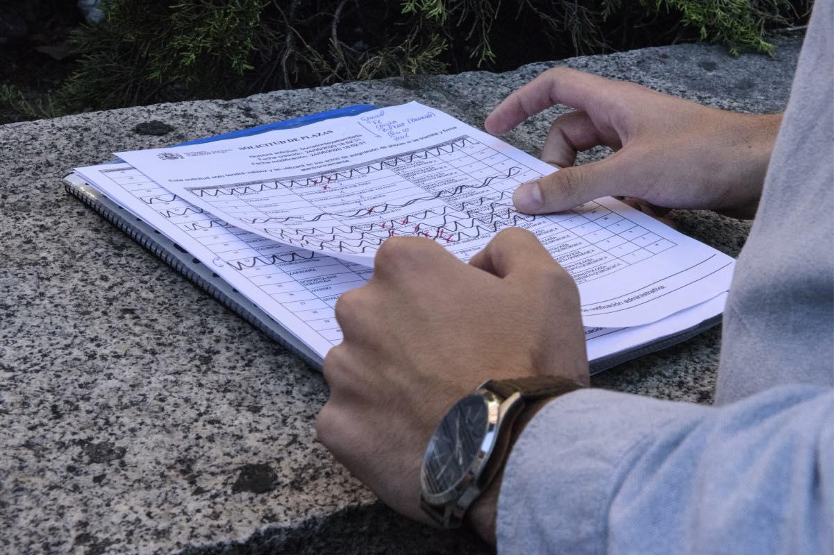 Uno de los aspirantes comprueba 'in situ' la evolución del listado de plazas durante el momento de la elección (Foto: Luis Camacho).