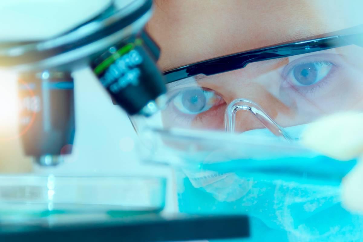 Mujer mirando por microscopio