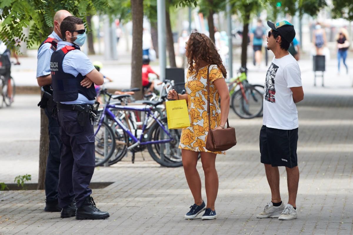 Unos agentes de los Mossos d'Esquadra informan a una pareja del uso obligatorio de la mascarilla, este viernes en Barcelona.EFE/ Alejandro García