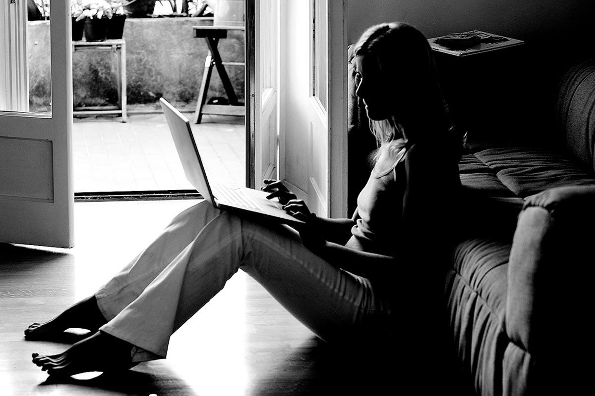 Mujer sentada en el suelo trabajando con un portátil
