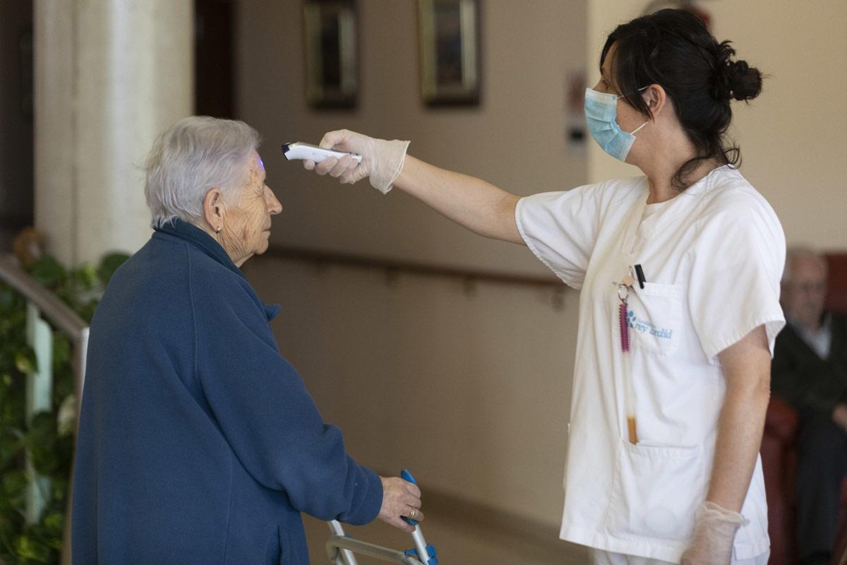 Enfermera tomando la temperatura a una anciana