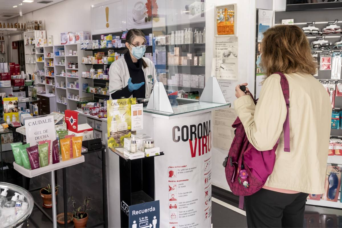 Una farmacéutica atiende a una mujer siguiendo las medidas de seguridad para evitar contagios.