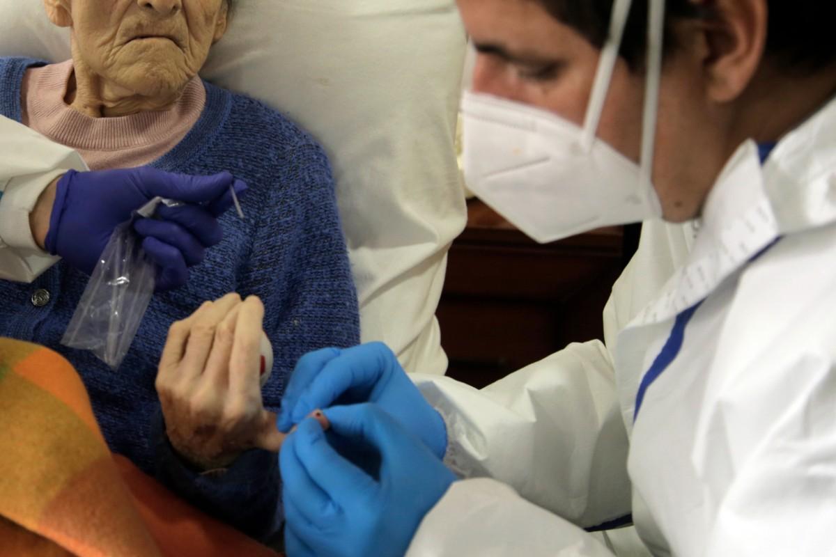 Sanitario realizando un test de Covid-19 a una anciana en una residencia de Pozuelo de Alarcón, en Madrid (Javier Barbancho)