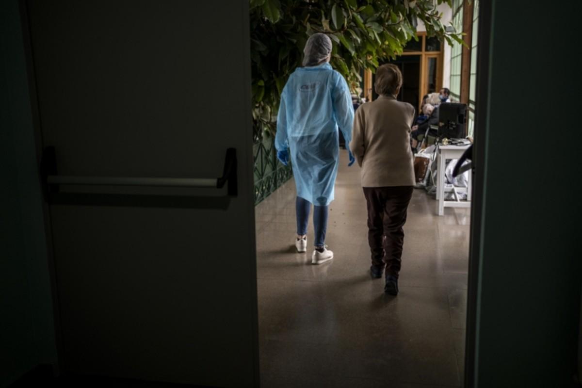 Un voluntario de MSF acompaña a una anciana en una residencia (Olmo Calvo/MSF)