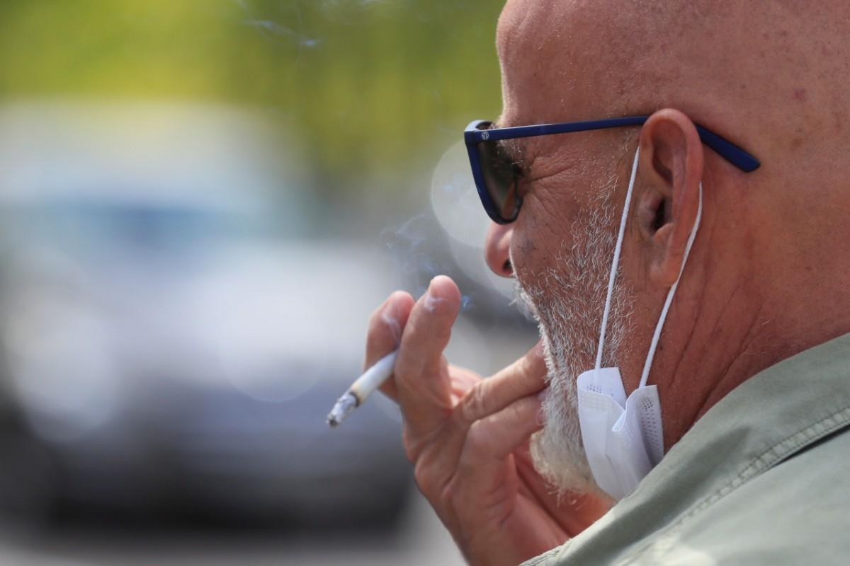 Un hombre fumando tras bajarse la mascarilla. (EFE/Fernando Alvarado)