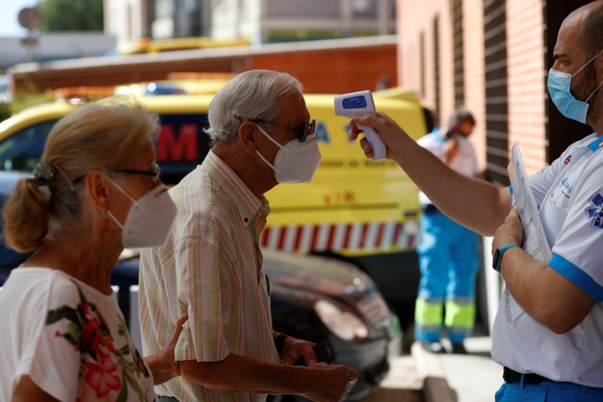 Un sanitario toma la temperatura a un hombre antes de acceder al Centro de Salud de Los Ángeles, en el distrito de Villaverde, donde el gobierno regional ha puesto en marcha uno de los dispositivos de pruebas PCR para tratar de detectar asintomáticos de 15 a 49 años en las áreas de la región con mayor incidencia de COVID-19. (EFE/Mariscal)