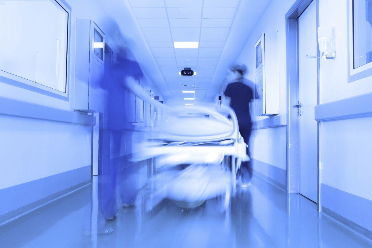 Una camilla avanza por el pasillo de un hospital.
