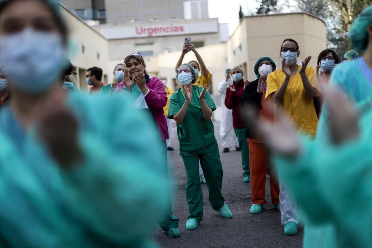 Varios profesionales sanitarios aplauden a las puertas de un hospital madrileño (Fotografía: Alberto Di Lolli).