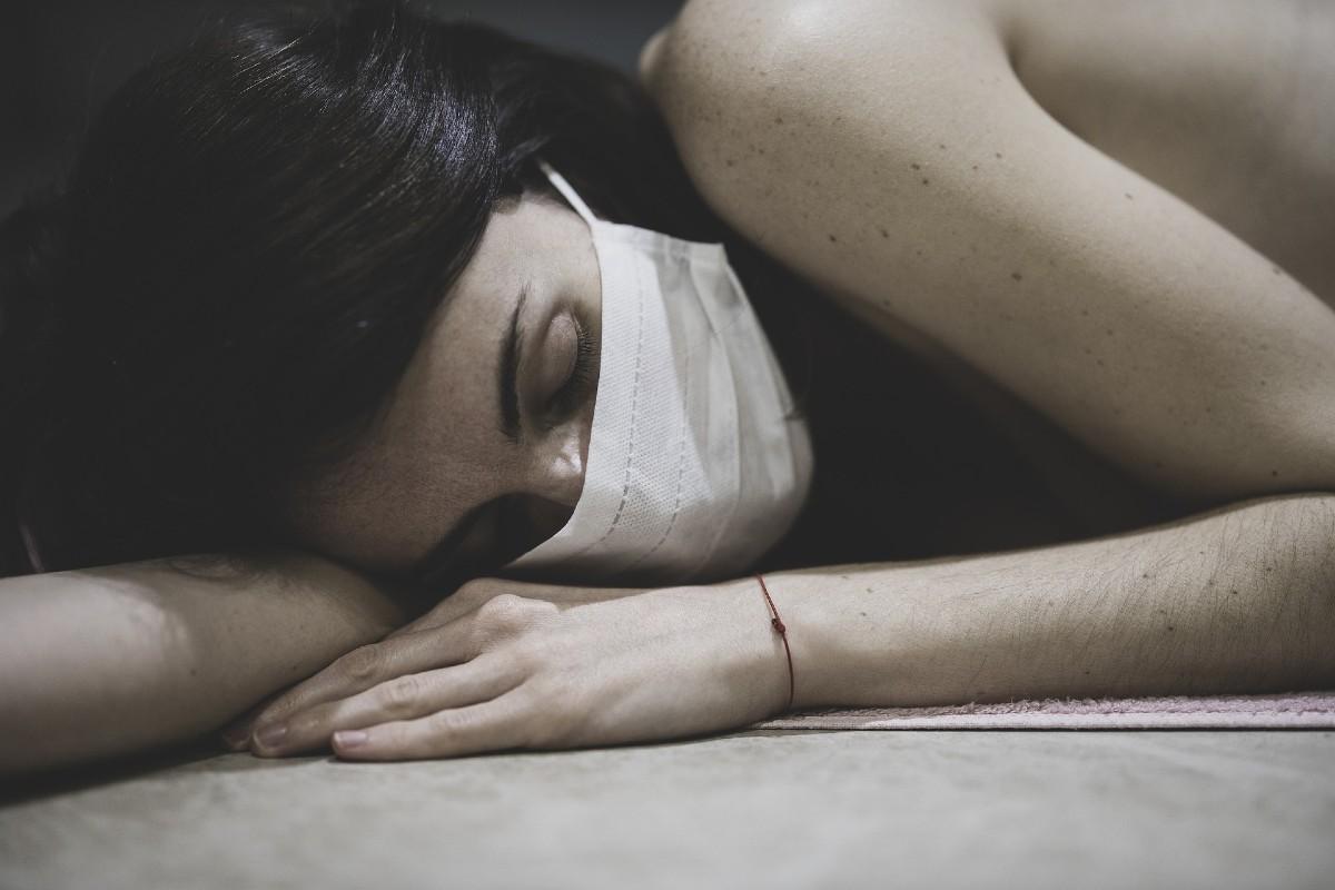 Mujer tumbada con mascarilla.