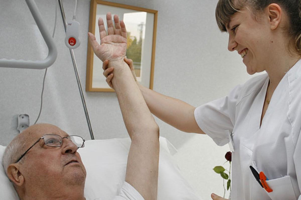 Una enfermera da cuidados paliativos a pie de cama a un enfermo en un centro de día