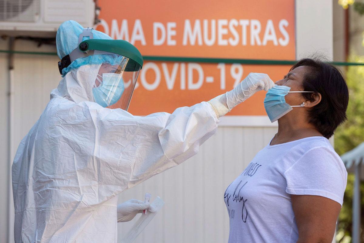 Una enfermera toma una muestras para una prueba PCR a una mujer
