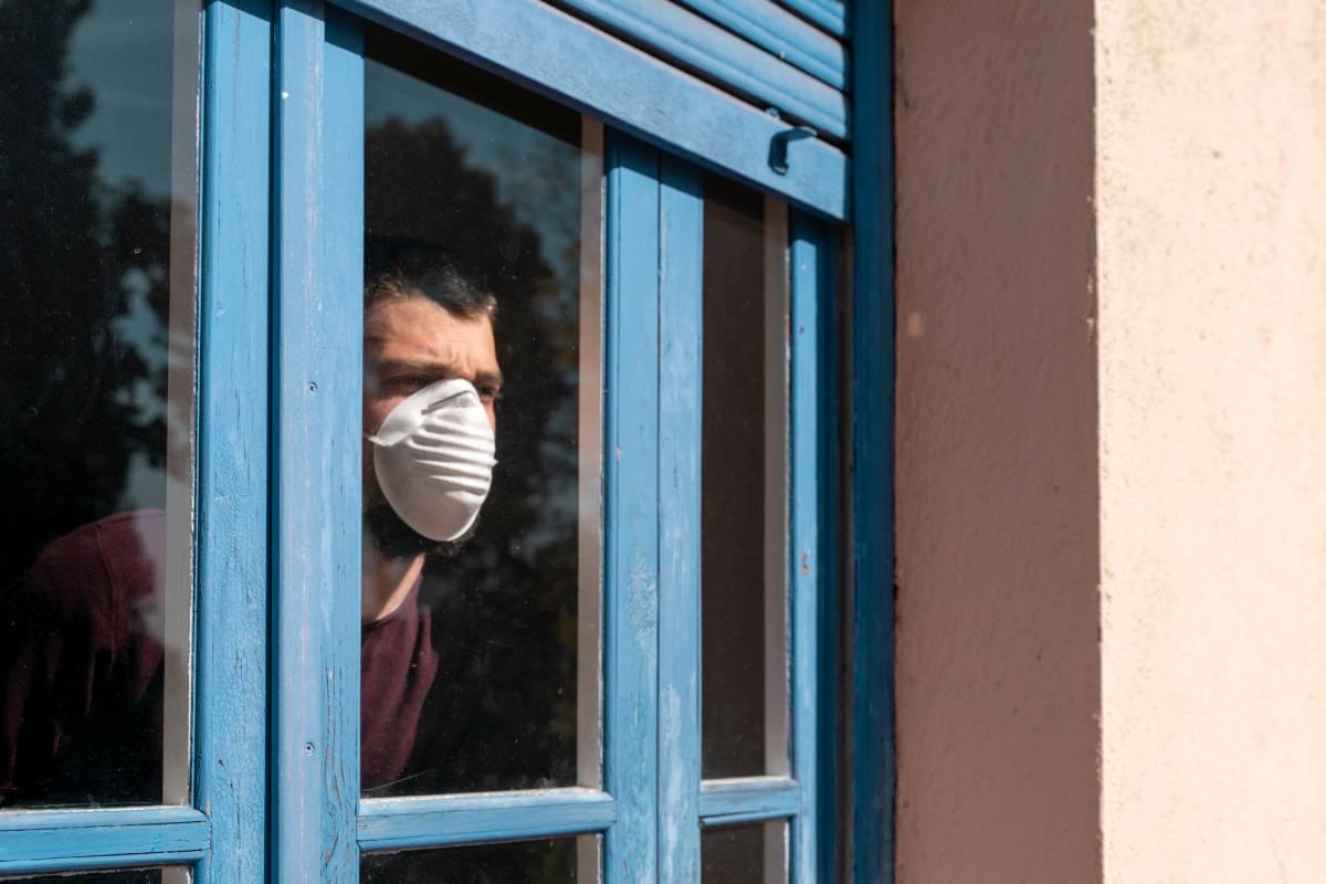 Hombre con mascarilla mirando por la ventana