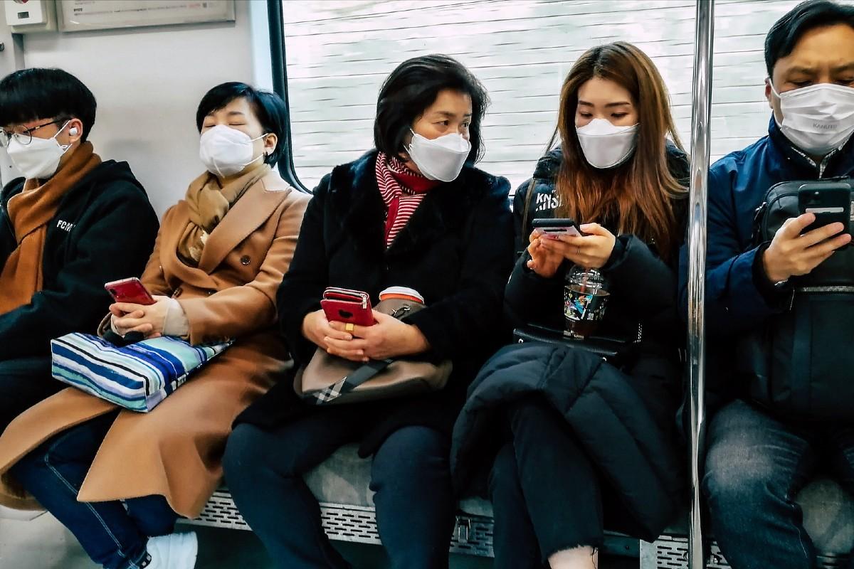 Varias personas en el metro con mascarillas.