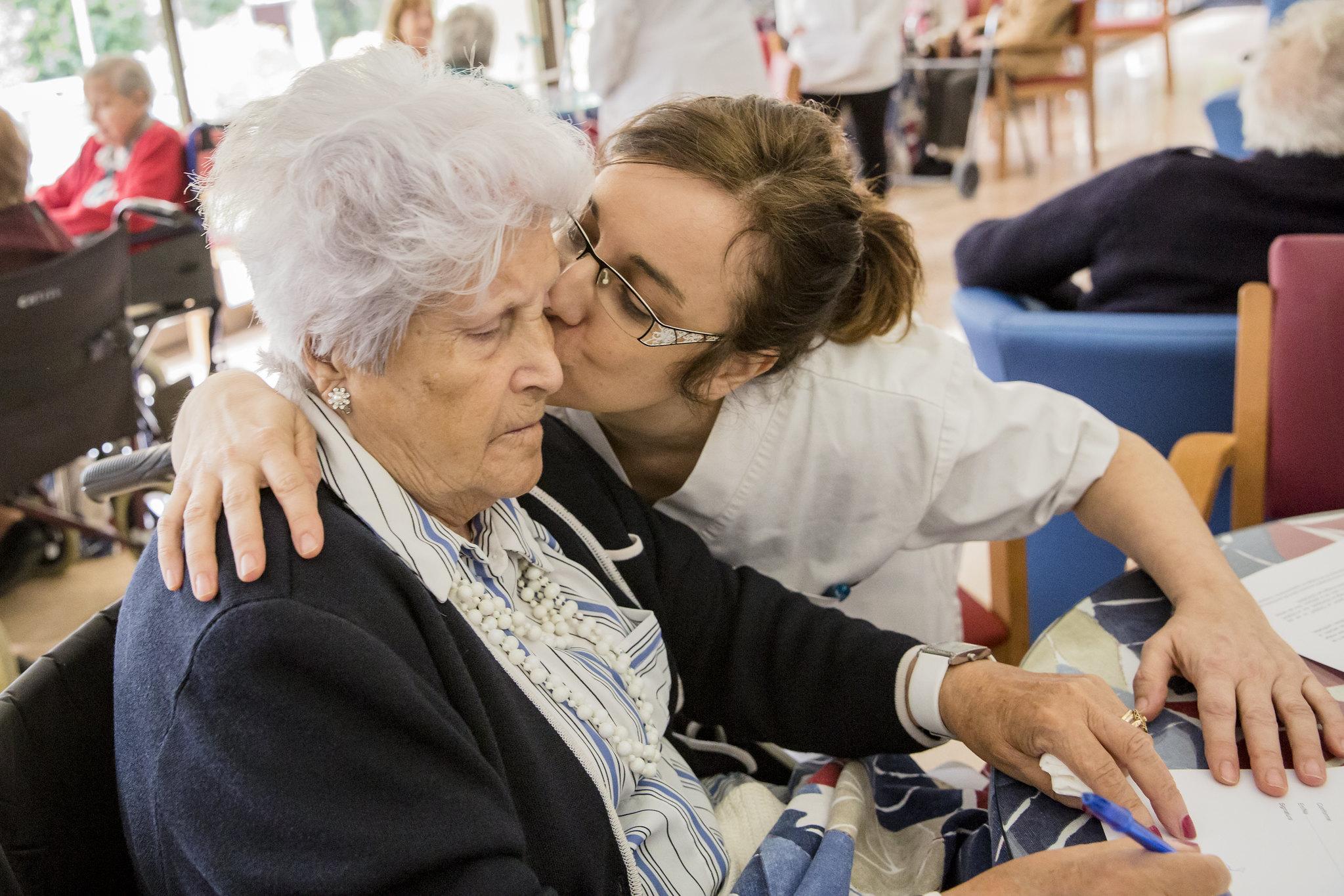 Una enfermera geriátrica dando un beso un paciente. FOTO: Ariadna Creus y Ángel García (Banc Imatges Infermeres).