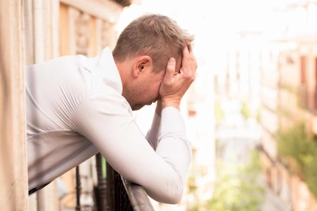 Un hombre muestra desesperación en un balcón.