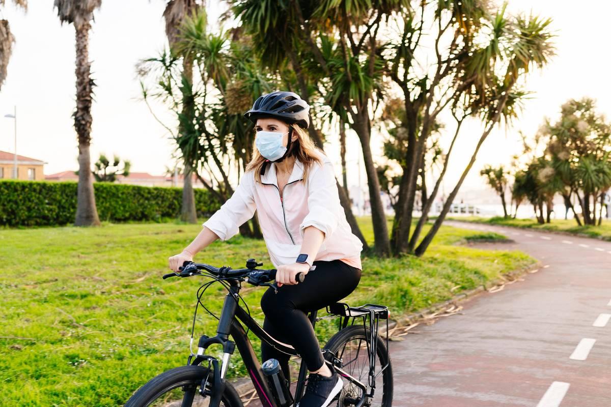 Mujer de paseo en bicicleta con mascarilla