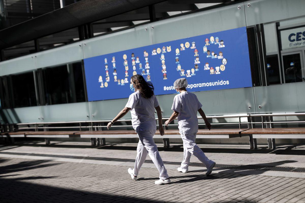 Dos profesionales sanitarias caminan ante las instalaciones del hospital provisional de IFEMA, en Madrid (Fotografía: Alberto Di Lolli).