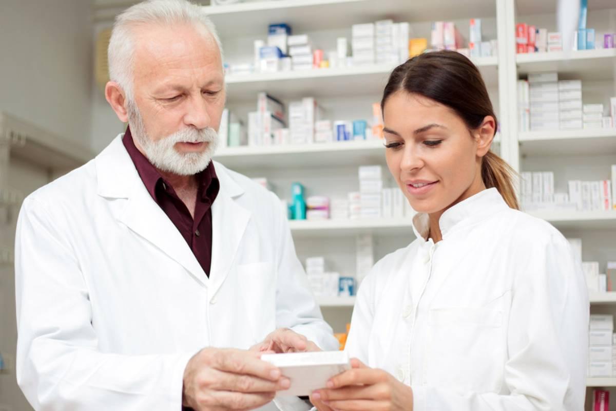 Una pareja de farmacéuticos revisando un medicamento.